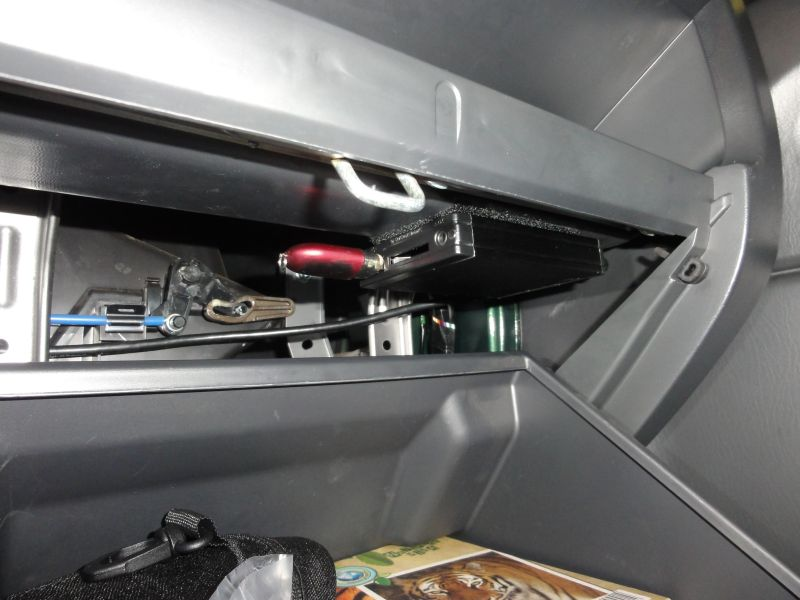 I suggest to to fix it under the top of the glovebox with a velcro hook.